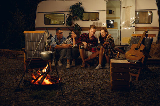 Friends sitting by campfire in the night, camping