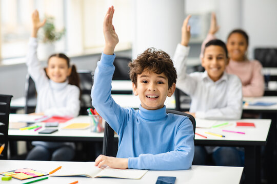Diverse small schoolkids raising hands at classroom