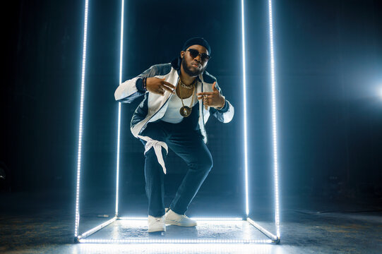 Stylish rapper in gold jewelry and sunglasses