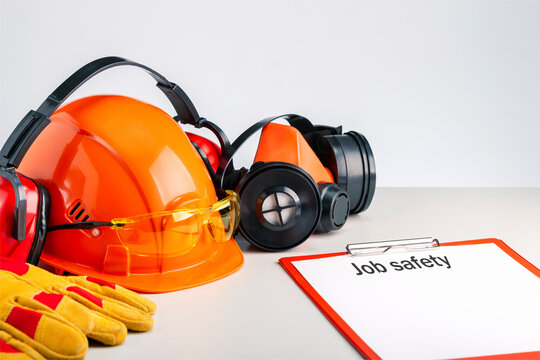 Job safety  write on a clipboard and personal protective equipment on the table.