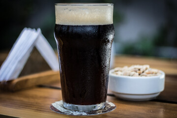 Obraz Black porter stout bock beer with foam in pint glass with peanuts on a wooden table - fototapety do salonu