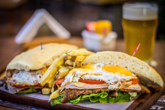 Milanesa argentinian steak sandwich with salad tomatoes cheese egg, chips and beer