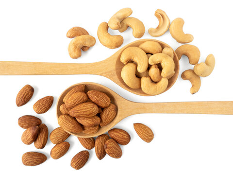 Organic almonds and cashew nuts in wooden spoon and heap almonds and cashew isolated  top view on white background for almond nuts can improve health concept.