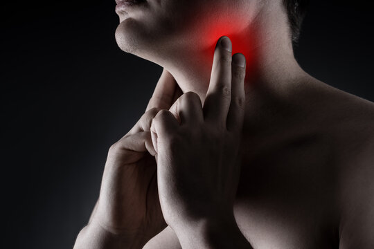 Sore throat, men with pain in neck on black background