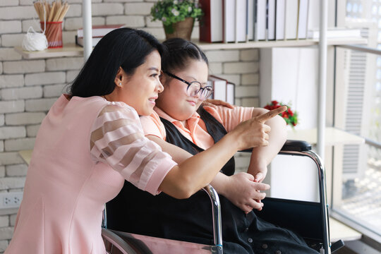 Asian mother with young girl with autism on wheelchair in room at home. Autistic young students and teachers smiling.