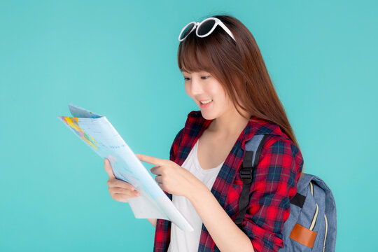 Beautiful happy young asian woman travel looking and pointing a paper map isolated on blue background, asia girl search journey with direction in vacation trip with cheerful for leisure.