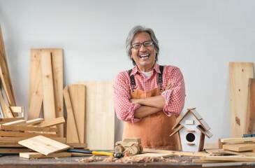 Fototapeta Asian senior carpenter man with crossed arms smile at home carpentry workshop obraz