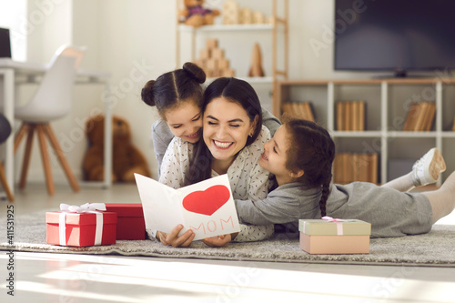 We love you. Smiling young woman getting presents from kids. Two cute twin daughters giving mom handmade greeting card. Little children lying on floor, hugging mommy and wishing her Happy Mother's Day
