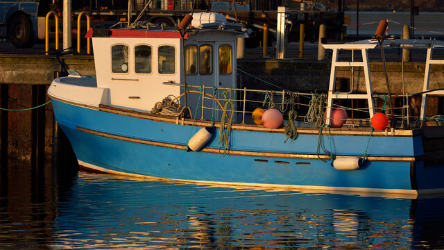 Fishing boat moored to a pier, close-up. A view of the shore of a small town Port Ellen at sunrise. Isle of Islay, Inner Hebrides, Scotland, UK. Transportation, nautical vessel