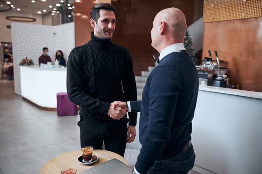 Two happy man shaking hands after making agreement