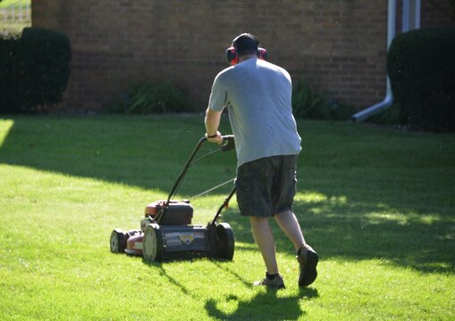 Rear View Of Man Mowing The Grass