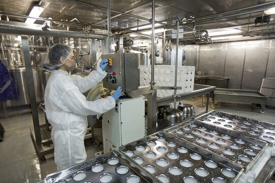 Background image of industrial conveyor belt at clean food production factory with unrecognizable female worker operating machine units, copy space