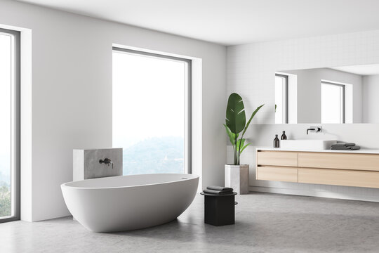 Interior of stylish bathroom with wooden walls, concrete floor, comfortable bathtub, double sink with horizontal mirror.