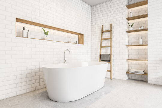White bathtub and brick wall, shelves with gels and plants, marble floor