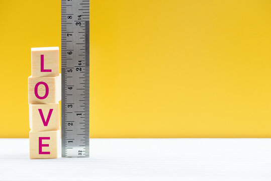 Measurement of love, quality and quantity, behavioral science concept : Square wood blocks with a word LOVE are measured by a metal ruler with centimeter scale over yellow background