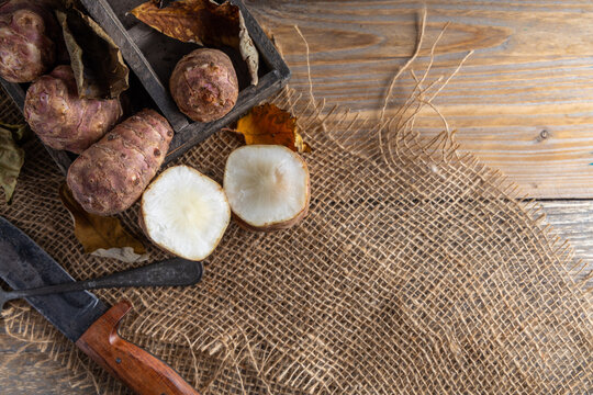 Trendy Winter vegetable. Jerusalem artichoke one of the forgotten vegetables who has become trendy again, on a wooden table.
