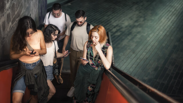 Group of friends talk on smartphones while standing on escalator. Modern people with cell phones outdoor. Mobile communication technology. High angle view