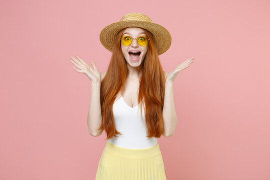 Young smiling shocked excited surprised caucasian nice redhead woman 20s ginger long hair wearing straw hat glasses summer clothes looking camera isolated on pastel pink background studio portrait.