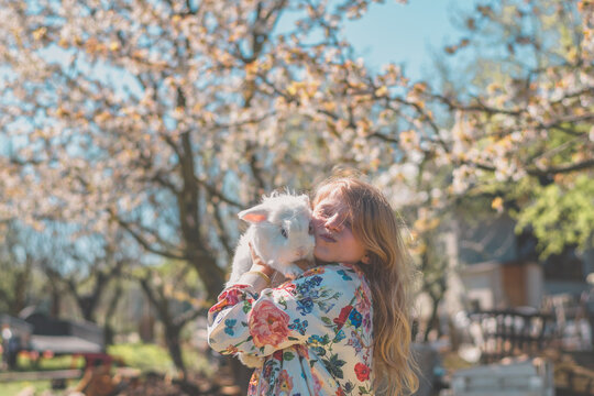 child with white rabbit under blooming white trees in spring Easter time