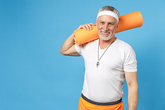 Elderly gray-haired sportsman rainer instructor smiling coach man 50s wearing sportswear white t-shirt holding yoga mat on shoulder isolated on blue background studio portrait. Fitness sport concept