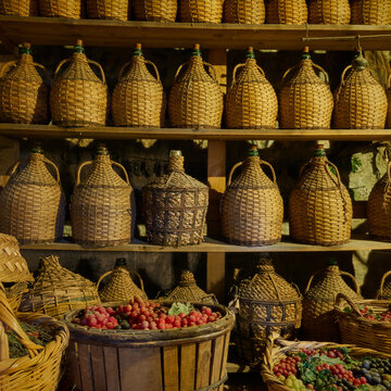 Wine bottles on shelves and baskets with grapes