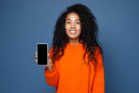 Smiling beautiful young african american woman wearing casual basic bright orange sweatshirt standing hold mobile cell phone with blank empty screen isolated on blue color background studio portrait.