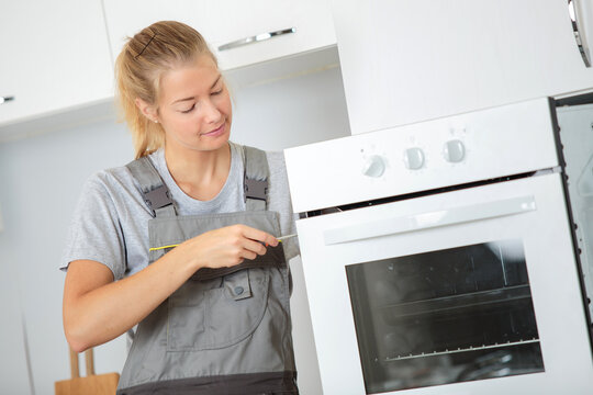 female electrician fixing oven unit