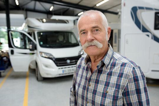 portrait of senior man in campervan garage