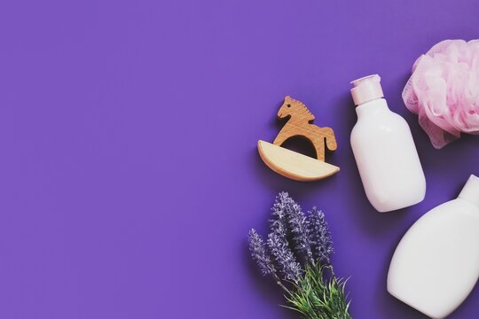 Eco friendly lavender baby bath care products on a purple background flat lay photography. White shampoo bottle, hair balm, pink sponge, flowers