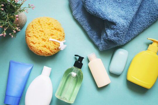 Bath products gift set top view photography. Different types shampoo, hair balm, conditioner, face cream, soap supplies, yellow sponge and blue towel