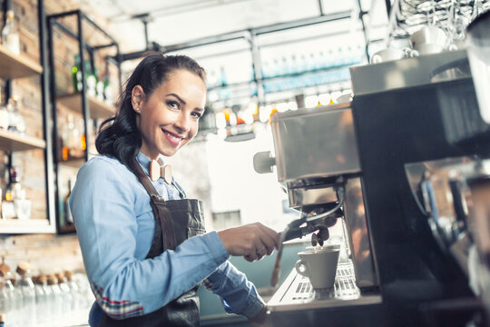 Beautiful barista makes espresso on a professional coffee maker in a cafe