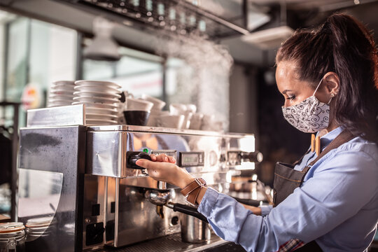 Face mask wearing waitress operates coffee machine in a cafe