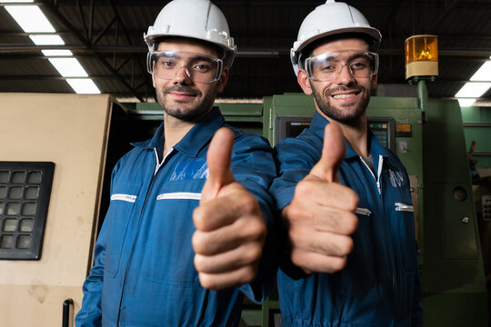 Two skillful factory engineer or worker showing teamwork and partnership . Industrial people and manufacturing labor concept .