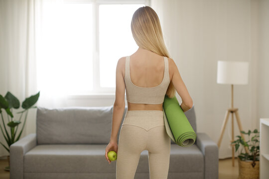 Woman with Yoga Mat and Apple at Home