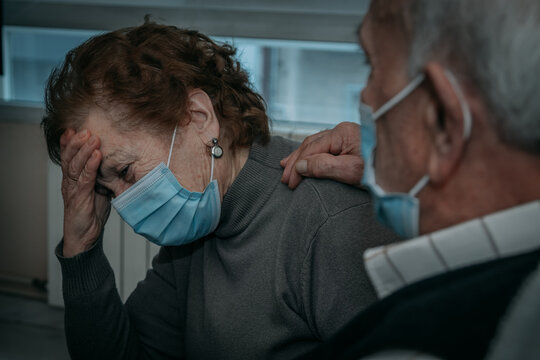senior couple wearing masks with coronavirus symptoms