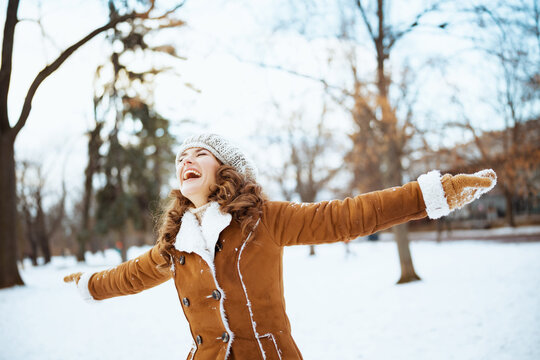 smiling stylish woman rejoicing outside in city park in winter