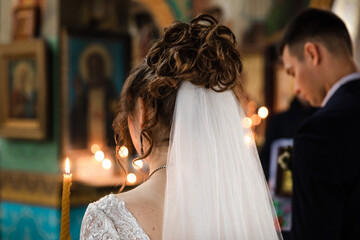 Church wedding. Bride wearing a white dress and a veil and groom from the back