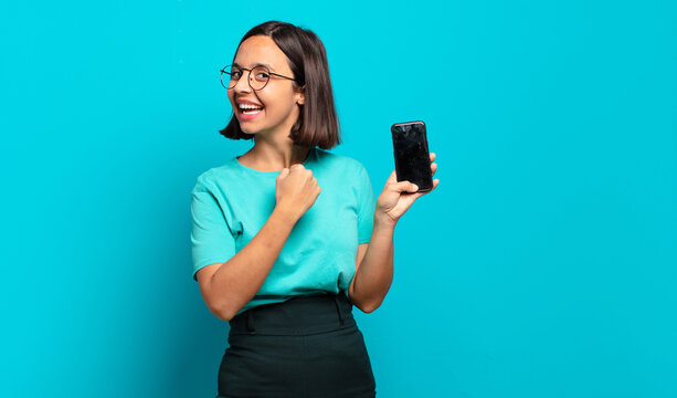 young hispanic woman feeling happy, positive and successful, motivated when facing a challenge or celebrating good results