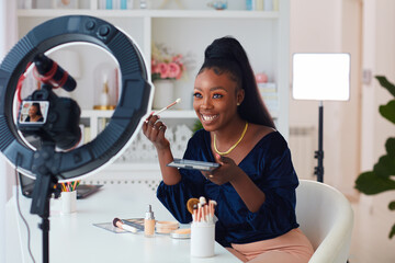 Fototapeta happy young african american woman streaming a beauty vlog from home, online content creator applying a makeup on obraz