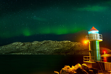 aurora in the sky, the ocean illuminated by lighthouses. night in skandywawi. Arctic Circle polar night
