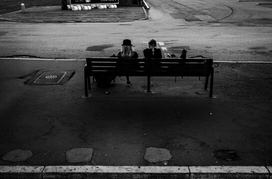 two girls sitting on the bench of the bus stop