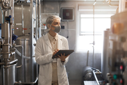 Waist up portrait of young woman wearing mask and holding digital tablet during quality control inspection in sunlit workshop at food factory, copy space