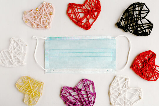 Knitted hearts and medical mask on white background. Valentine's Day during the coronavirus pandemic. Happy Valentine's Day 2021. Copy space for the text