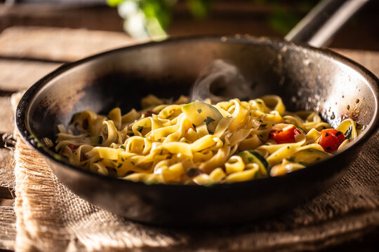 Vegetarian tagliatelle with zucchini and tomatoes served in sizzling hot pan