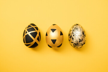 Easter golden decorated eggs on yellow background. Minimal easter concept. Happy Easter card with...