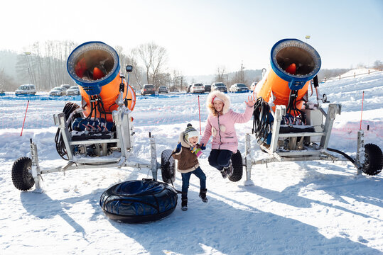 boy and girl jumping near the snow cannon and tubing