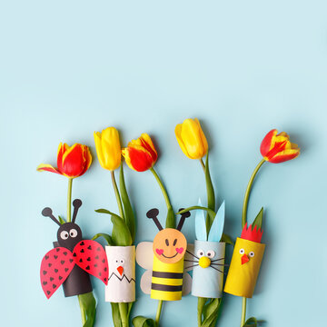 Happy easter spring toy collection and fresh flowers on blue background, kids holiday party concept background. Paper crafts, DIY. creative idea from toilet roll. reuse, recycle