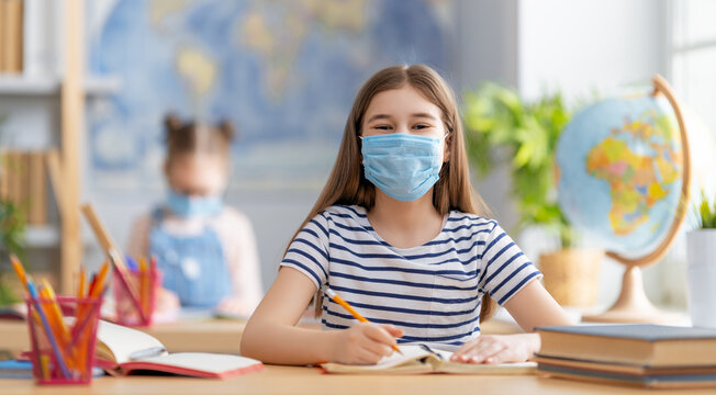 Kids are wearing facemasks learning in class
