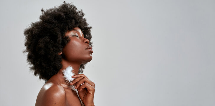 Portrait of sensual african american woman with afro hair touching her glowing skin with white feather, posing with eyes closed isolated over gray background