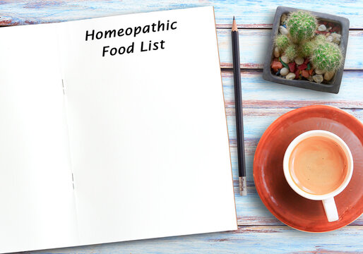 Homeopathic food list text on blank notebook,pencil and coffee on wood table background